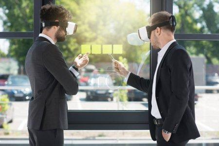Photo pour Hommes d'affaires portant des écouteurs de réalité virtuelle tout en travaillant dans le bureau - image libre de droit