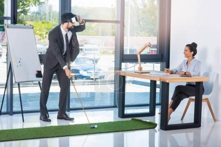 Photo for Businessman playing golf in vr headset while colleague sitting at workplace in office - Royalty Free Image