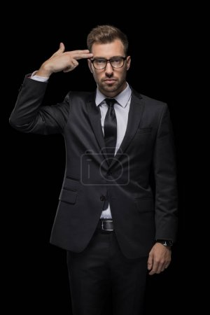 Photo for Handsome depressed businessman in black suit with hand gun sign, isolated on black - Royalty Free Image