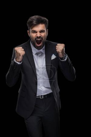 Photo pour Bel homme d'affaires excité célébrant le succès, isolé sur noir - image libre de droit