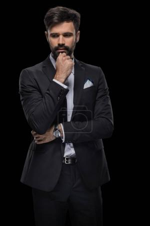 Photo for Handsome bearded pensive businessman in black suit, isolated on black - Royalty Free Image
