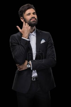 Photo for Handsome bearded businessman in bow tie and black suit, isolated on black - Royalty Free Image