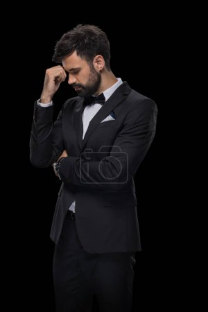 Photo for Handsome bearded upset businessman in bow tie and black suit, isolated on black - Royalty Free Image