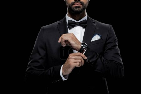 Photo for Cropped view of businessman in bow tie and tuxedo with watch, isolated on black - Royalty Free Image