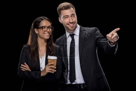 Photo for Happy businesswoman in formal wear drinking coffee, while businessman pointing somewhere, isolated on black - Royalty Free Image