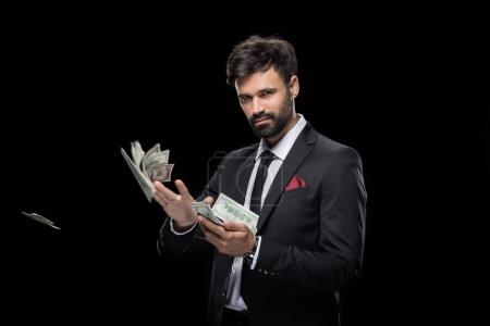 Photo for Handsome rich businessman throwing dollar banknotes, isolated on black - Royalty Free Image