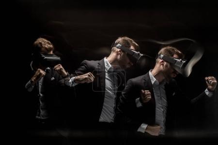 Foto de Exposición múltiple de hombre de negocios de perforación y el uso de casco de realidad virtual, aislado en negro - Imagen libre de derechos