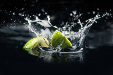 Photo pour Tranches de lime fraîche tombant dans l'eau avec éclaboussures isolées sur fond noir - image libre de droit