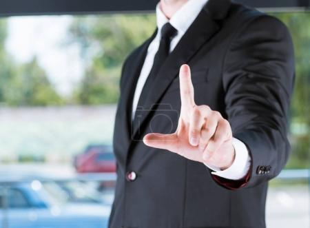 Photo for Cropped view of businessman in black suit pointing with finger - Royalty Free Image