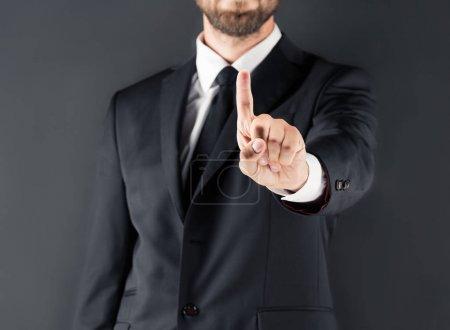 Photo pour Vue recadrée d'homme d'affaires en costume pointer avec le doigt, isolé sur fond gris - image libre de droit