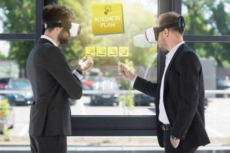 Photo for Businessmen wearing virtual reality headsets discussing business plan on window in office - Royalty Free Image