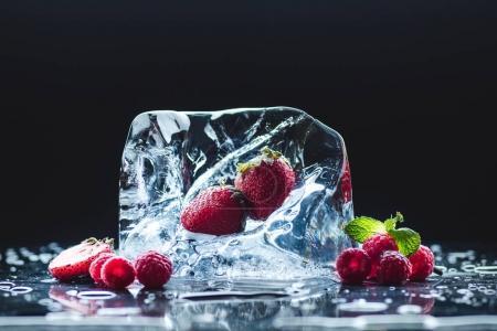 Photo pour Vue rapprochée des fraises rouges mûres et framboises et fusion du glaçon sur fond noir - image libre de droit