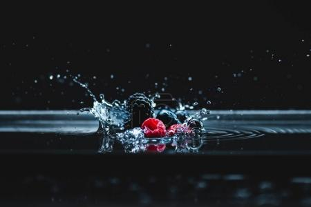 Photo for Close-up view of ripe fresh juicy berries falling in water with slashes on black - Royalty Free Image