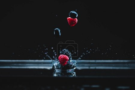 Ripe berries falling in water