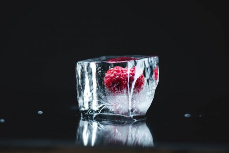 Photo for Close-up view of ripe juicy raspberry frozen in ice cube on black - Royalty Free Image