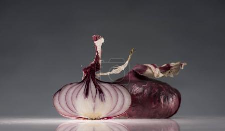 Photo for Halves of ripe red onion on reflective surface isolated on grey - Royalty Free Image