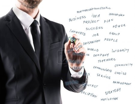 Businessman writing on glass panel