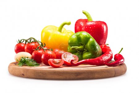 Photo for Tomatoes and different peppers on wooden cutting board, isolated on white - Royalty Free Image