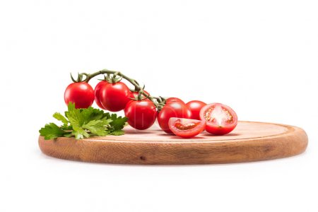 Photo for Fresh red cherry tomatoes and parsley on wooden cutting board isolated on white - Royalty Free Image
