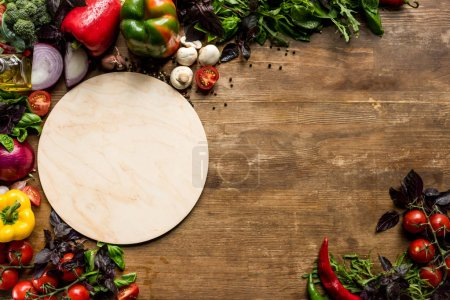 Photo for Top view of wooden board and fresh pizza ingredients on table - Royalty Free Image