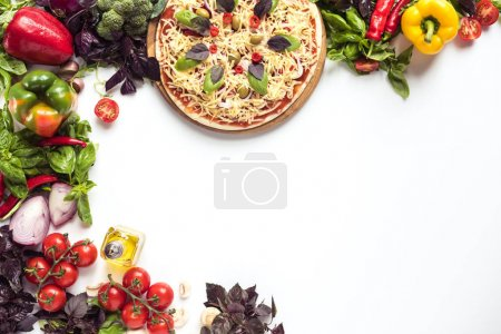 Photo for Top view of homemade italian pizza on wooden board and fresh vegetables isolated on white - Royalty Free Image