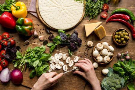 Photo for Top view of woman cutting on wooden board while making homemade pizza - Royalty Free Image
