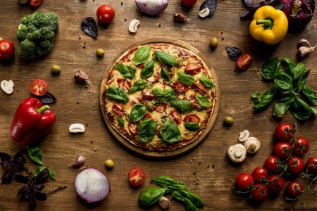 Photo for Top view of pizza with fresh herbs on wooden board and various ingredients on table - Royalty Free Image