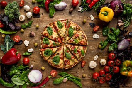 Photo for Top view of cut italian pizza, fresh vegetables and herbs on wooden tabletop - Royalty Free Image