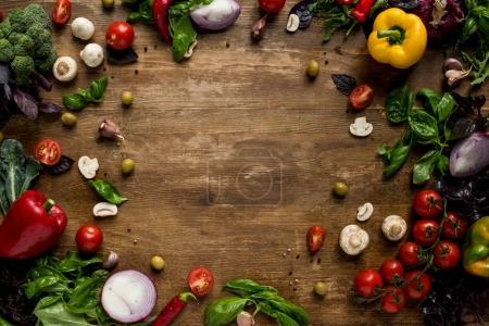 Photo for Top view of various fresh vegetables and herbs on wooden tabletop - Royalty Free Image
