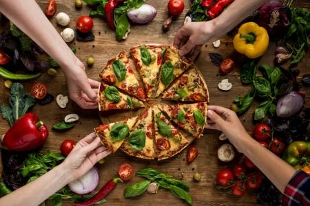 Photo for Partial view of friends taking homemade pizza slices - Royalty Free Image