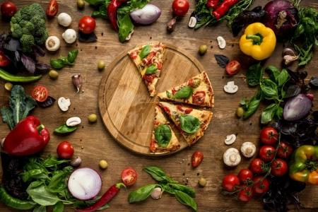 Photo for Flat lay with italian pizza slices on wooden board with various fresh vegetables and herbs on table - Royalty Free Image