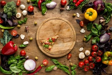Photo for Flat lay with pizza slice on wooden board with fresh vegetables, spices and herbs on table - Royalty Free Image