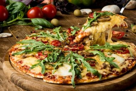 Photo for Close up of sliced hot italian pizza with fresh arugula - Royalty Free Image