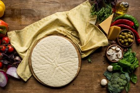Photo for Top view of raw pizza dough and fresh ingredients on wooden tabletop - Royalty Free Image