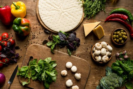 Raw pizza dough and vegetables