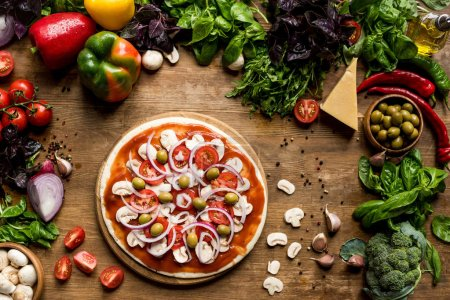 Photo for Top view of raw homemade pizza with fresh vegetables on wooden tabletop - Royalty Free Image