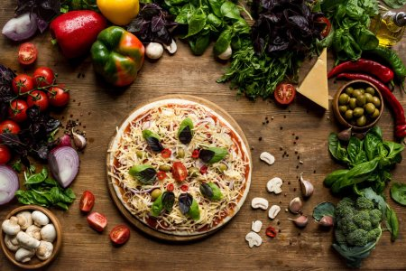 Photo for Top view of raw homemade pizza with cheese and fresh vegetables on wooden tabletop - Royalty Free Image