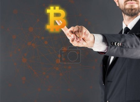 Photo for Cropped view of businessman in suit pointing with finger on bitcoin sing, isolated on grey - Royalty Free Image