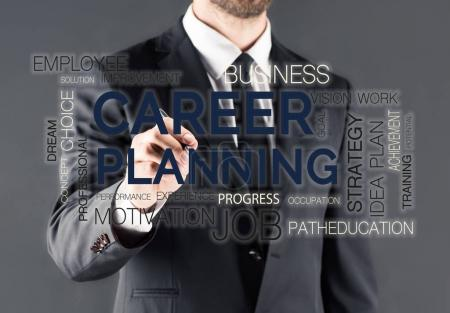 Businessman writing on glass panel