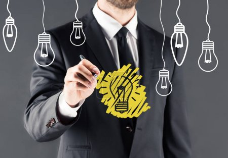 businessman drawing light bulb