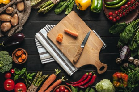 Photo for Top view of cutting board with carrot and knife and organic fresh vegetables around on wooden tabletop - Royalty Free Image