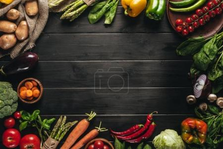 Photo for Frame of organic fresh vegetables on sacking on wooden tabletop with copy space - Royalty Free Image