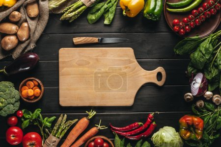 Photo for Top view of cutting board with knife and organic fresh vegetables around on wooden tabletop - Royalty Free Image