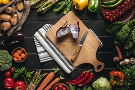 Photo pour Vue du dessus de la planche à découper avec oignon et couteau et légumes frais biologiques sur table en bois - image libre de droit