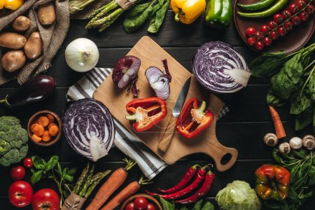 Photo for Top view of cutting board with knife and organic fresh vegetables on wooden tabletop - Royalty Free Image