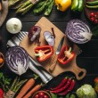 Top view of cutting board with knife and organic f...