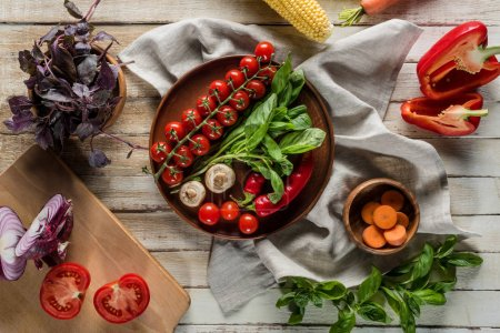 Photo for Top view of organic fresh vegetables with napkin on wooden tabletop - Royalty Free Image