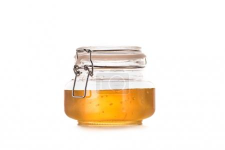 Photo for Close-up view of fresh sweet honey in glass jar isolated on white - Royalty Free Image