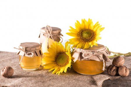 Sunflowers and honey in glass jars