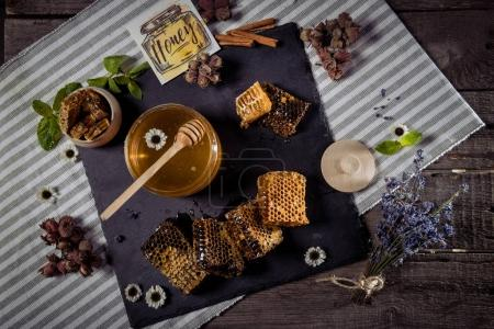 Photo for Top view of fresh sweet honey in glass jar with honey dipper, honeycombs and card with inscription honey - Royalty Free Image